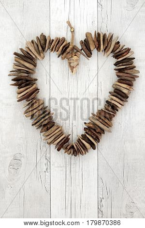 Rustic driftwood heart on distressed white wood background.