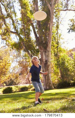 Boy Throwing Disk In Park