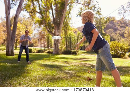 Father And Son Throwing Disk In Park Together