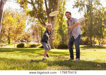 Father Teaching Son To Throw Disk In Park