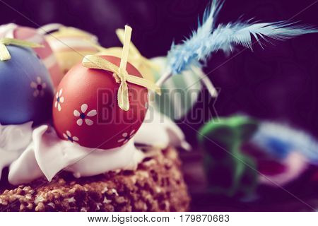 a mona de pascua, a cake eaten in Spain on Easter Monday, topped with different decorated eggs and feathers of different colors, with a retro filter effect