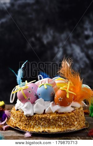 a mona de pascua, a cake eaten in Spain on Easter Monday, topped with different decorated eggs and feathers of different colors, on a rustic wooden surface