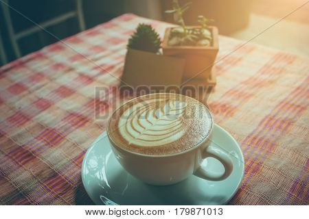 A Latte art hot Coffee cup on wooden desk.