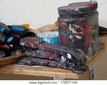 paint crusted jars and stapler in an artist's studio