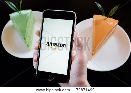 CHIANGMAI - THAILAND JAN 29 2017: Amazon application on Apple iPhone 6s wich Matcha green tea and ice tea cake in coffee shop. Amazon is an American electronic e-commerce company distribution worlwide