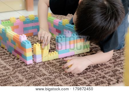 young man playing plastic block at Nursery between waiting parent.