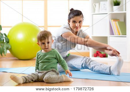 Active adult woman is engaged in fitness and yoga at home. Her son baby by near sitting and playing.
