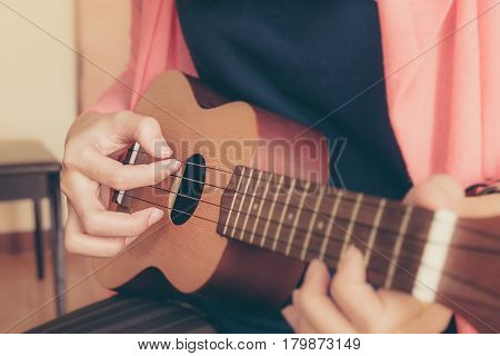 A woman playing ukulele in close up view.