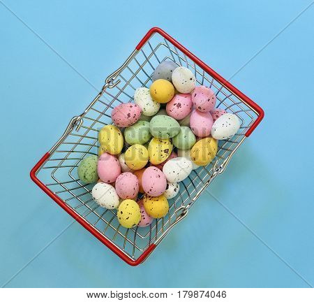 Small Painted Chocolate Eggs In A Small Supermarket Basket On A Blue Background.