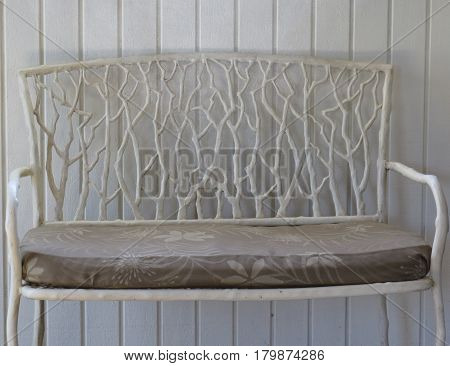 Wooden tree branch bench awaits a sitter against a white backdrop