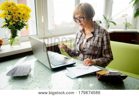The elderly woman works behind the laptop. On a table various receipts and accounts lie. Modern pensioners use modern technologies.