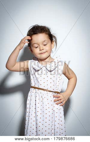 Portrait of 3 year old little girl with dress, thinking on bright white background