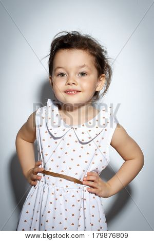 Portrait of 3 year old little girl with dress, smiling and posing on bright white background