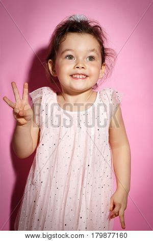Portrait of Happy 3 year old little girl with dress showing three fingers on bright pink background