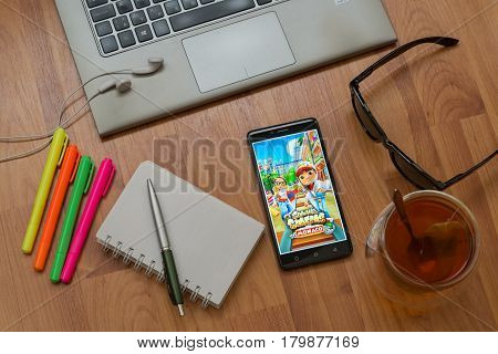 Nitra, Slovakia, april 3, 2017: Subway surfers application in a mobile phone screen. Workplace with a laptop, an earphones, notepad, pen, tea, sunglasses and color markers on wooden background