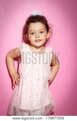 Portrait of 3 year old little girl with dress posing on bright pink background