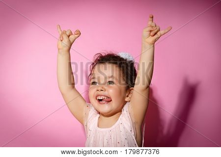 Portrait of 3 year old little girl with dress, showing horns on hands, dance screaming on rock concert on bright pink background