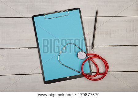 Blank Clipboard And Stethoscope On Wooden Background