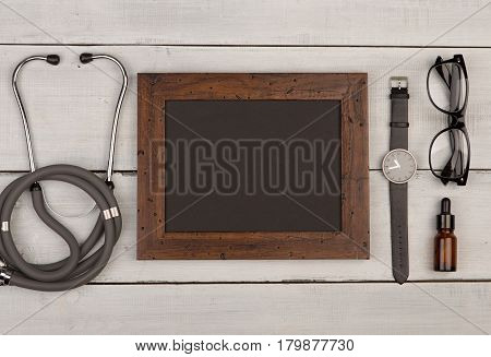 Blank Blackboard, Stethoscope, Eyeglasses And Watch On Wooden Background