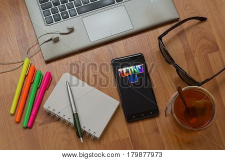 Nitra, Slovakia, april 3, 2017: Tetris application in a mobile phone screen. Workplace with a laptop, an earphones, notepad, pen, tea, sunglasses and color markers on wooden background