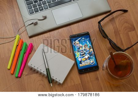 Nitra, Slovakia, april 3, 2017: Clash Royale application in a mobile phone screen. Workplace with a laptop, an earphones, notepad, pen, tea, sunglasses and color markers on wooden background