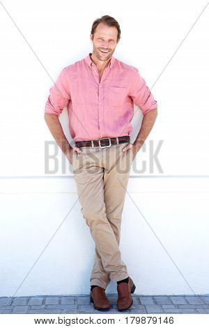 Full Length Smiling Older Man Leaning Against White Wall