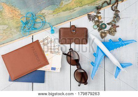 Plane, Map, Passport, Money, Wallet, Sunglasses On White Wooden Table