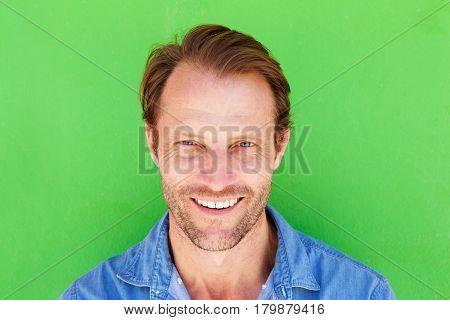Happy Older Man Smiling Against Green Background