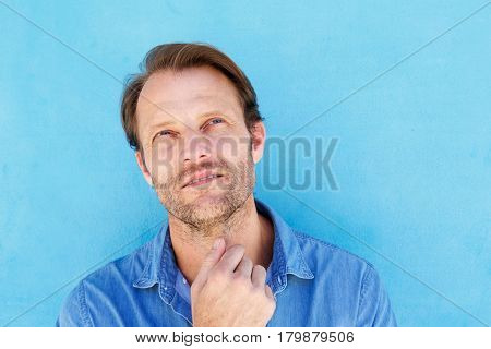 Handsome Man Thinking With Hand To Chin Against Blue Wall
