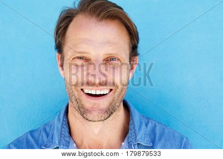 Close Up Attractive Male Model Smiling Against Blue Wall