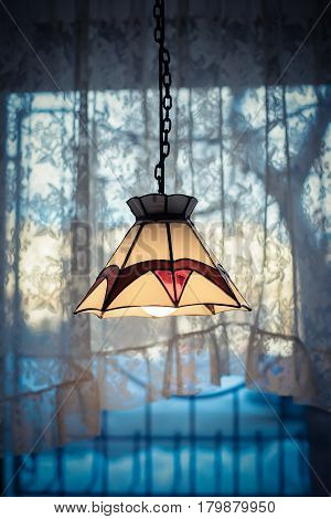 The old warm colored lampshade on the lamp on the background of the window in the evening