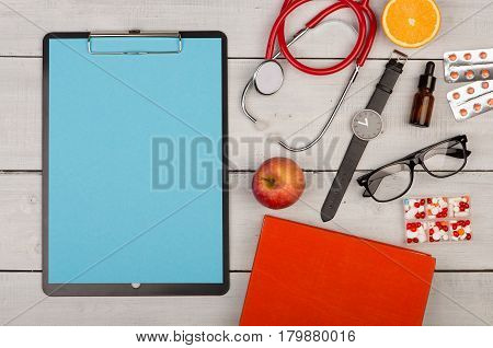 Blank Clipboard, Pills, Fruits, Book, Stethoscope, Eyeglasses And Watch On Wooden Background
