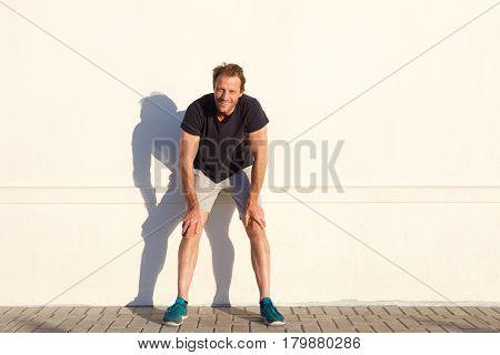 Full Length Sports Man Resting Against Wall