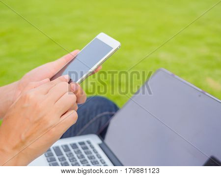 Pretty Young woman using smart phone. Female working on cell phone on green grass field