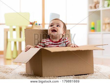 Cute smiling baby boy sitting inside brown cardboard box