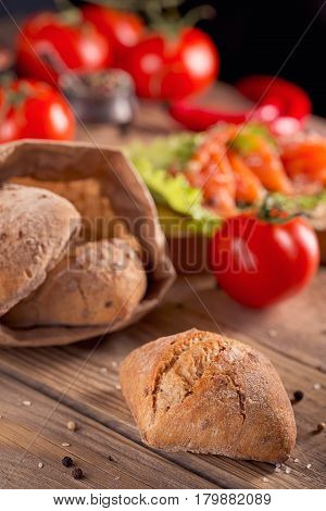 Multigrain bread with slices of smoked salmon chili pepper and tomatoes on rustic wooden background.