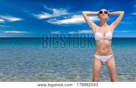 Happy woman is standing in sea water
