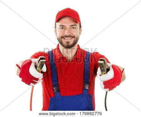 smiling car mechanic with jumper cables isolated on white background