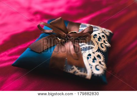 Weddings ring on the blue pillow on red background