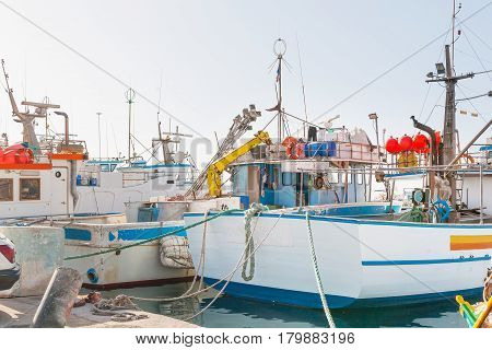 Rigging of the boat. The stern of the yacht with equipment and fasteners. Two fishing ships moored in sea port Marsaxlokk Malta.