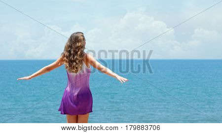 Freedom woman in dress happy and free open arms on beach at sunny day. Beautiful pretty woman looking at horizont smiling by the ocean during summer holidays vacation.