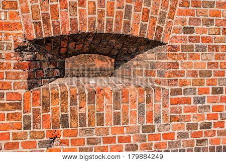 loophole in the wall with red bricks of the old fortress