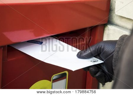 Sending a letter. Putting it to the red post box