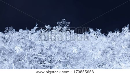 Xmas natural ornament of snowflakes in snowbank micro-structure at snowy christmas night