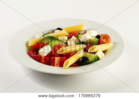 Tasty beautiful greek traditional greek or italian salad with vegetables and pasta on plate. Bright Background.