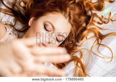 Beautiful young woman hiding her face of camera
