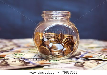 Glass jar with coins on the black background. A lot of dollar bills