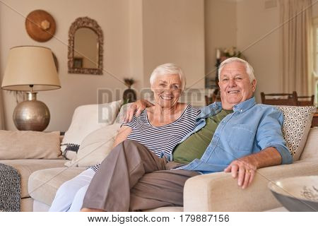 Portrait of a smiling senior man with his arm around his wife's shoulder sitting together on their living room sofa at home