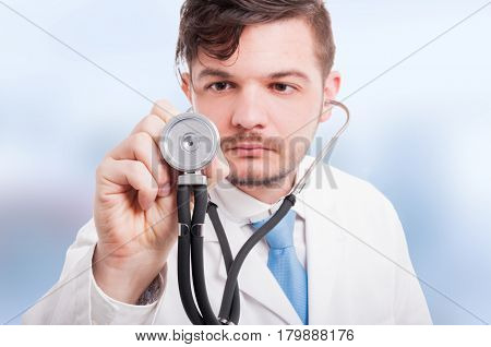 Close-up Of Young Male Doctor Listening With Stethoscope