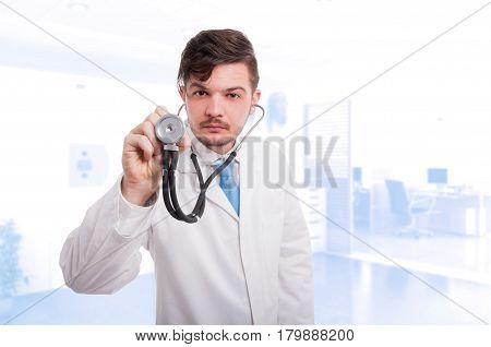 Male Cardiologist Listening Patient Heartbeat With Stethoscope